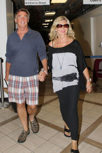 Olivia Newton-John Photos Photos - Olivia Newton-John and her husband John Easterling hold hands as they make their way through the LAX airport. - Olivia Newton-John and Her Husband Hold Hands at LAX