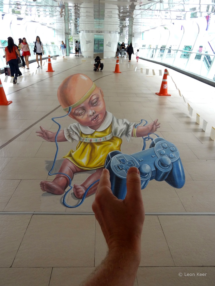 3d street art by Leon Keer at Living Arts Festival Bangkok. The painting is called 'Victim of circumstance'. The image shows a baby-child in control by a game-controller as a metaphor for child abuse.  Invite and organization of the festival by Wetalkchalk.