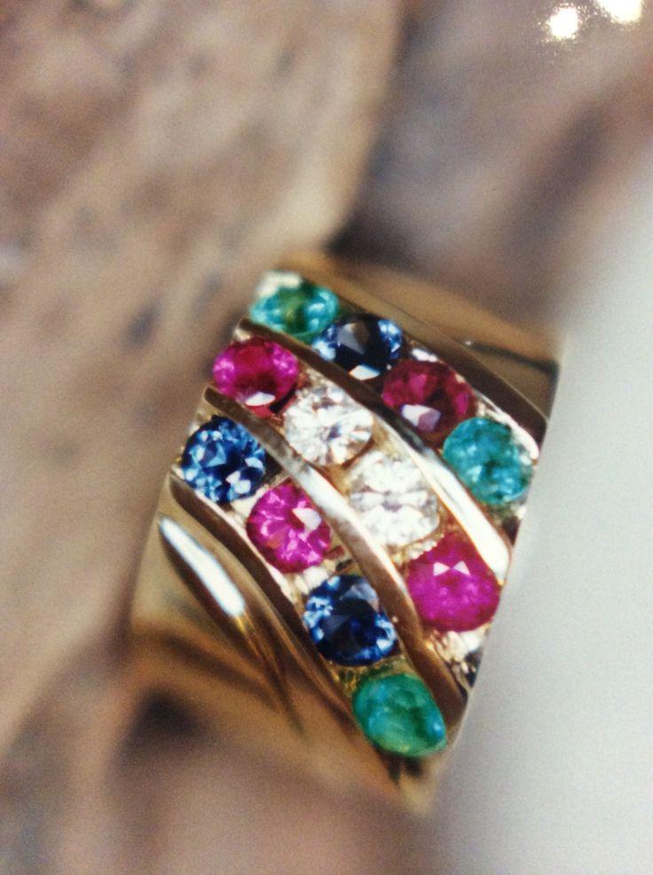 Multi colour Saphire Ruby Emerald an Diamond channel set ring in a fan influenced desighn