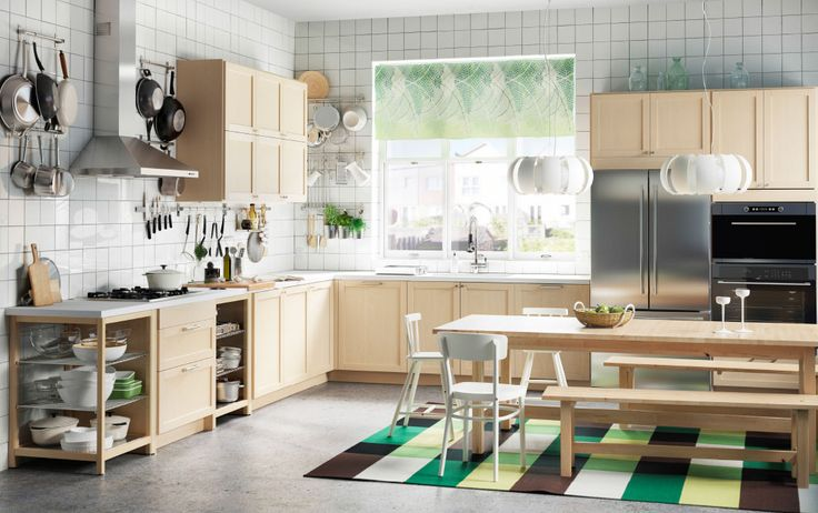 A kitchen with birch drawers, doors and a large kitchen table with benches and chairs