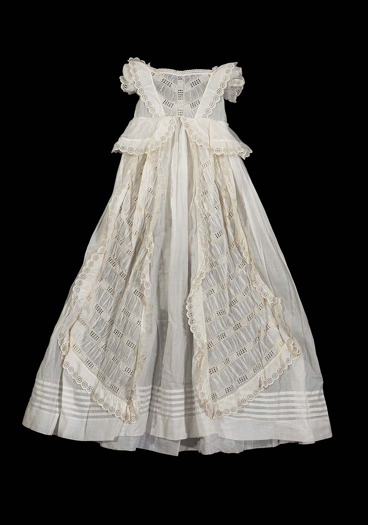 Made for Professor Fowler, of sheer white cotton, square cut neck, very short puffed sleeves, ruffled cape over sleeves running from waist line front to waist line back, peplum at waist line, two panels down skirt front of alternating bands of gathered self material and eylet embroidery, same ornament in center front of bodice, very narrow eyelet embroidery arond neck, around all other edges, except for bottom of skirt, a wide ruffle of eyelet embroidery in wheel design, five tucks above hem…