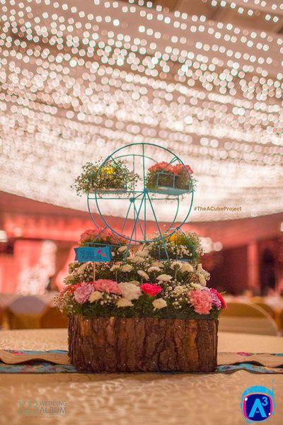 wooden logs , floral arrangements , roses in in table centerpiece , ferris wheel centerpieces