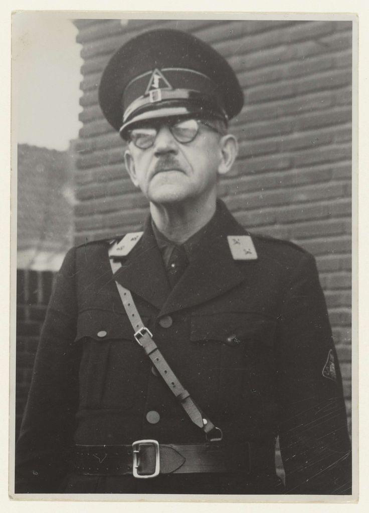 Fotodienst NSB | Portret van een lid van de WA, Fotodienst NSB, 1940 - 1944 | Portret van een lid van de WA. Gefotografeerd vanaf de taille, staand voor een huis. Op zijn kraag een distinctief met twee sterren: Kompaan, het lager kader. Pet met de Wolfsangel, op zijn linkermouw het driehoekige embleem van de NSB. Riem schuin over de borst. Het is een oudere man, met bril en snor. Het betreft dezelfde man als op NG-2007-35-206, het zou dus gaan om een lid van de Landwacht, opgericht eind…