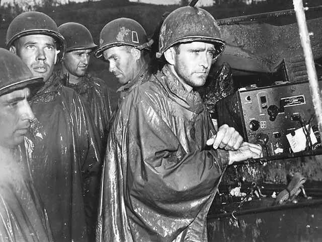 American soldiers of the 77th Infantry Division on Okinawa listen impassively to radio reports of Victory in Europe Day on May 8 1945.