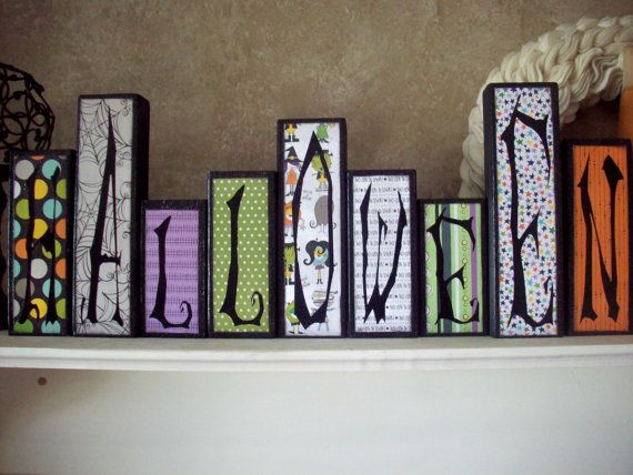 """These fun Halloween wood blocks look great on a mantle or table. These cute decorative wood blocks are great for decorating your home or for putting out during the holidays and parties. These blocks are made of wood, painted and covered with adorable patterned paper. The black letters are vinyl.    Block Sizes: This block set ranges from 5"""" to 9"""" tall and are about 2"""" thick  Paint: black  Paper: Halloween themed  Vinyl: black matte"""