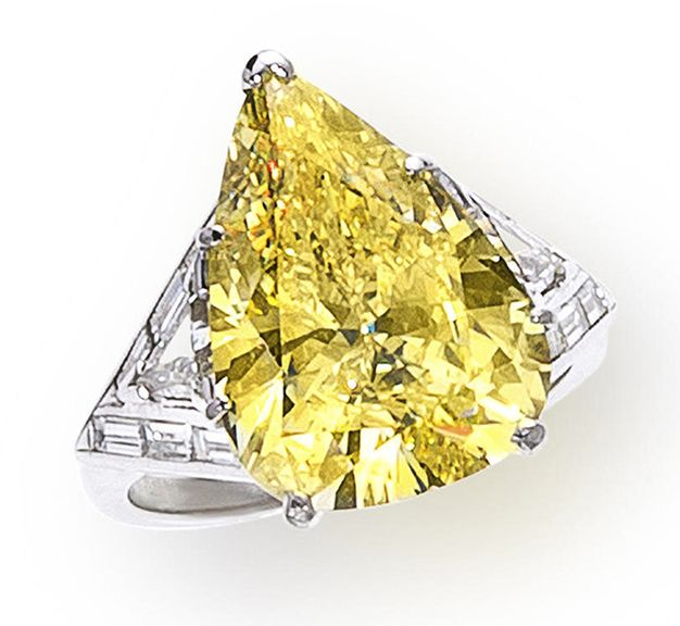 A fancy colored diamond and diamond ring centering a pear-shaped fancy intense yellow diamond, weighing 8.50 carats, flanked by triangular and baguette-cut diamond geometric shoulders and a plain mount