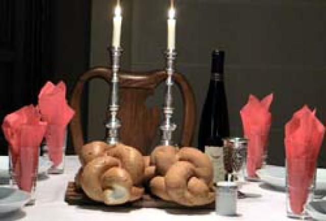 The Jewish Sabbath table includes candles, two loaves of challah, and wine. - Giora Shimoni