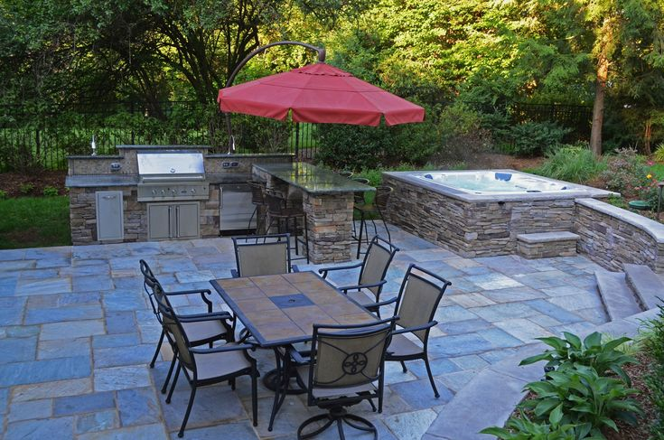 Stone patio and hot tub | The natural stone walls and patio create a well-defined outdoor living ...