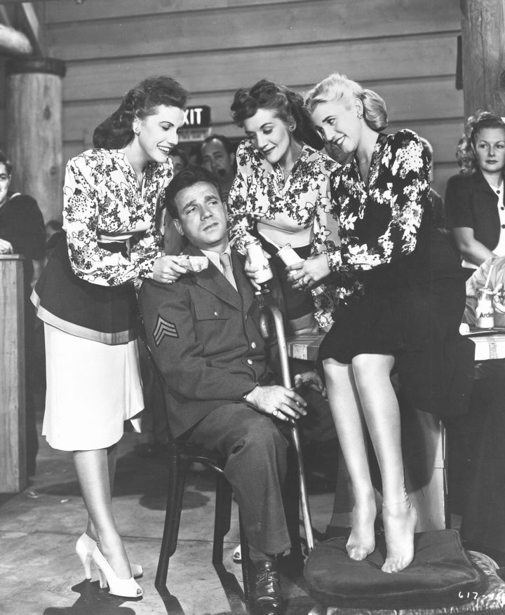 Dane Clark Is Surrounded By The Andrews Sisters In The Film Hollywood Canteen