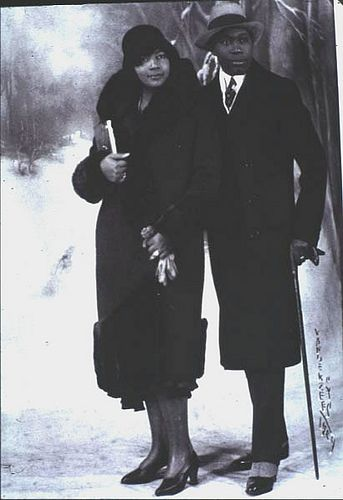 Headed Out On the Town, 1930's  An African American couple strike a pose in front of a winter landscape background in photo by James Van Der Zee