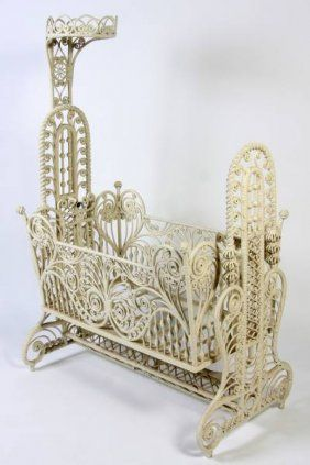 "Victorian white painted wicker cradle. American, early 20th century. With tall support mounted with a crown above rectangular cradle having scolled and turned open work frame. Height 63 1/2"", width 43"", depth 24""."