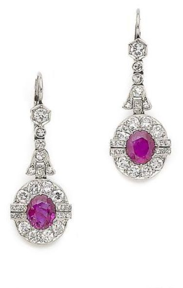 A pair of art deco ruby and diamond pendent earrings, first half of the 20th century Each oval-cut ruby, within a brilliant and single-cut diamond surround, suspended from an articulated row of similarly-cut diamonds with fleur-de-lys detail, millegrain-set throughout.: