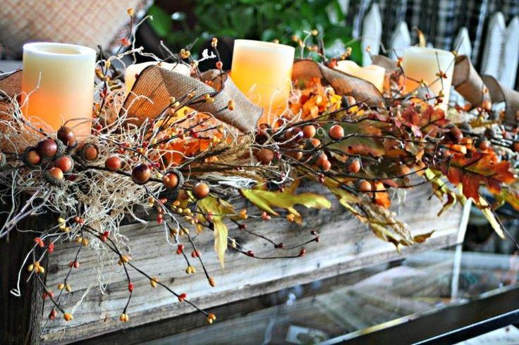 décoration de table automne - arrangement de brindilles, baies, feuilles, bougies cylindriques et nœuds de jute dans une boîte de bois