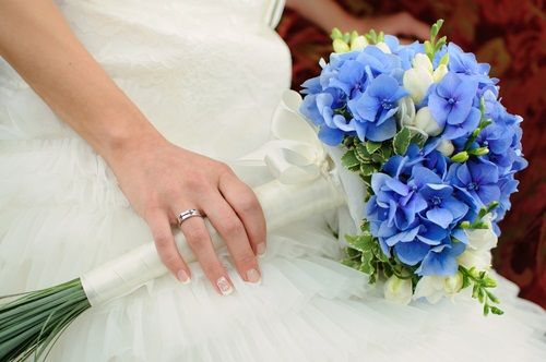 blue bridal bouquets - blue hydrangeas, white freesias, pittosporums wrapped with china grass, then wrapped with white ribbon