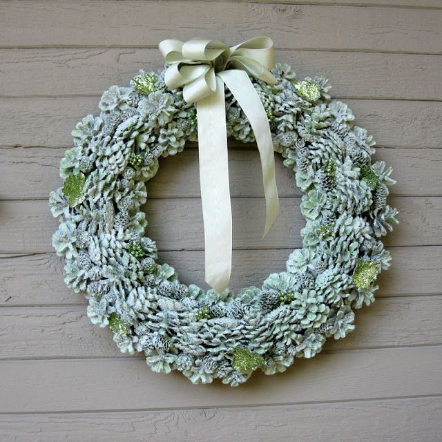 Making a pine cone wreath on a wire form.