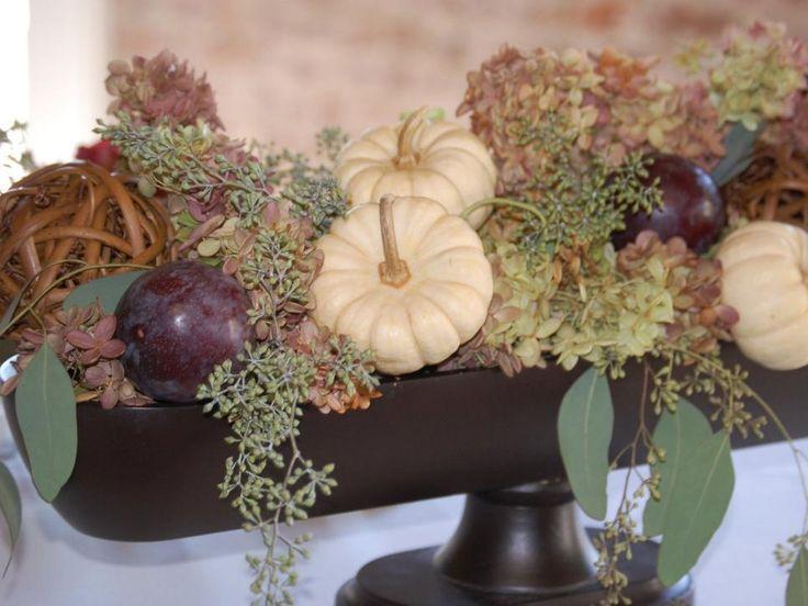 Une longue, urne pieds élève cette faible, pièce maîtresse rustique avec hortensia, eucalyptus et des formes rondes répétées dans le mini-citrouilles, des prunes et des balles de brindille. Obtenez artisanat pour faire votre propre.