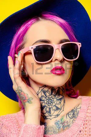 La muchacha bonita con el pelo carmes que llevaba ropa brillante y gafas de sol que presentan sobre  Foto de archivo