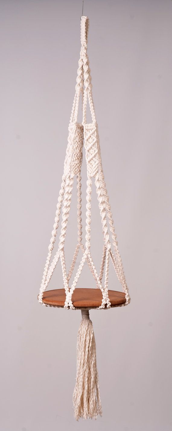 Macrame hanging table, creamy off white 5 mm braided cotton Cord. Many knots and variations give this table an interesting look. The cradle can hold larger pots or a tray, glass or wooden bowl (30 cm diameter). The overall look of the hanging table/plant holder will change depending on which type of container is used. length of 115 cm to a brush and 165 cm with brush It is shown with a 30 cm wooden tray.  The UV resistant cord is suitable for indoor and outdoor. This is for the hanger only…