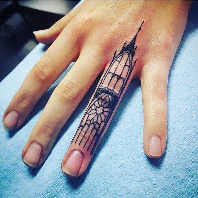 Bonita mano con tatuaje de torre en  un dedo