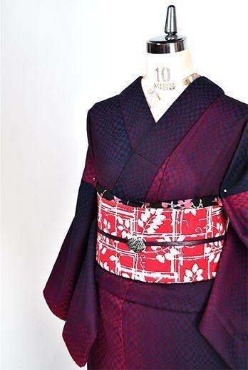 レイビーブルーとルージュレッドのバイカラーが織りなす市松模様がグラフィカルな曲線のパターンと大胆なグラデーションストライプを浮かびあがらせるトリックアートのようなデザインが印象的なウールの単着物です。