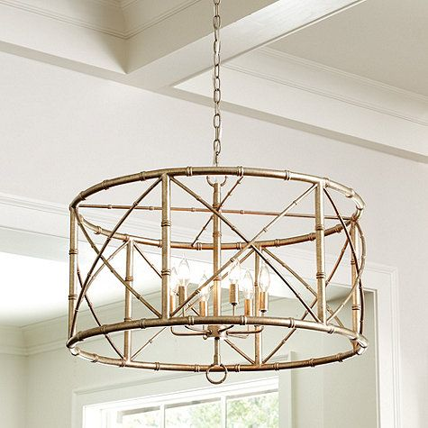 This light, airy Bamboo 6-Light Chandelier adds global flavor that layers easily with everything from antiques to modern mix. Metal frame has bamboo details and different size stocks for rich visual texture. Drum design allows it to be hung close to the ceiling. Bamboo 6-Light Chandelier features:Golden champagne finishRing finialsMetal frame