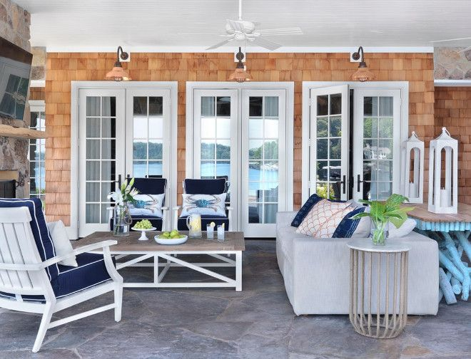 Cape Cod Style Home Boasts A Covered Patio Featuring Copper Barn Lights  Placed On Shingled Exterior Walls Over White Glass Panel French Doors.