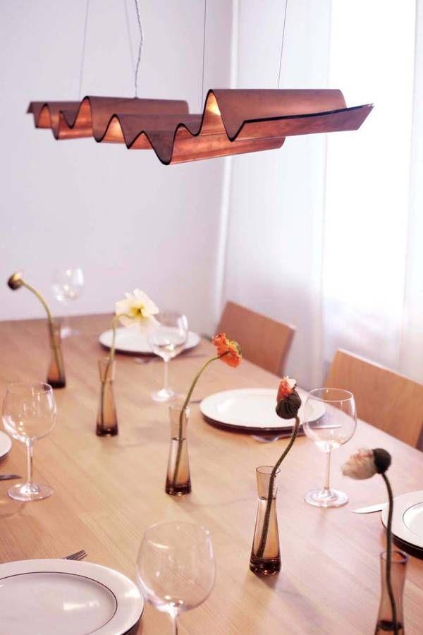 Eine Welle aus glänzendem Kupfer schwebt an dünnen Drahtseilen und inszeniert so jede Tischrunde mit ihrem wunderbar brillantem Licht.