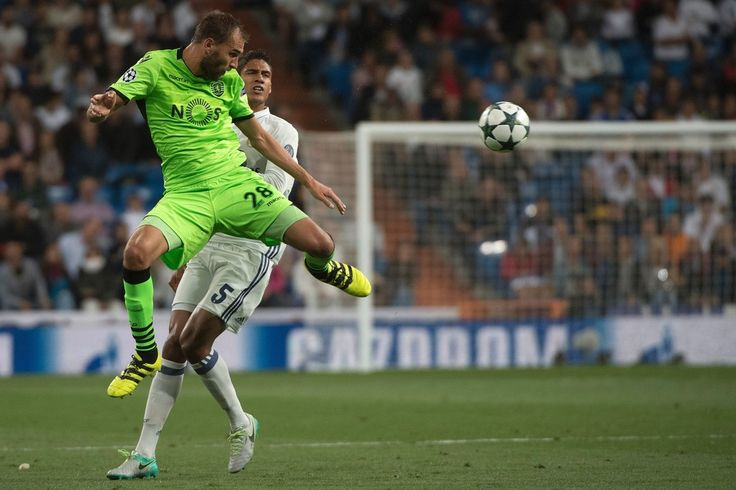 Sporting's Dutch forward Bas Dost vies with Real Madrid's French defender Raphael Varane during the UEFA Champions League football match Real Madrid CF vs Sporting CP at the Santiago Bernabeu stadium in Madrid on September 14, 2016.
