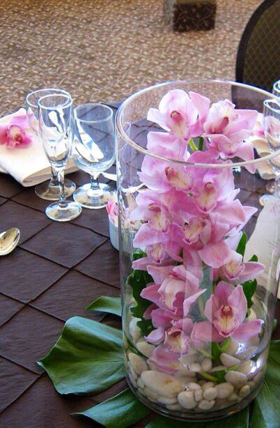 Cymbidium orchid with river rock and monstera leaf