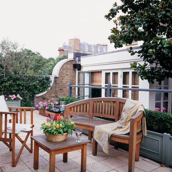 Paved roof garden with wooden bench, small wooden table and throw