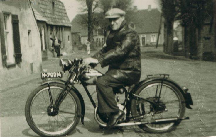Dit is kapper Willem van de Donk, alias Wim Blom, op zijn motor in de Dorpsstraat te Rosmalen. Links vooraan zie je de boerderij van Joh. van Nuland, daarachter het huisje van Betje van de Donk. Zoon Frans staat voor de deur. Op de achtergrond de boerderij van Piet van Wanrooij.