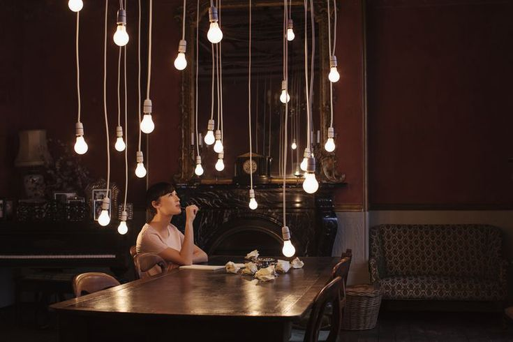 A woman sitting at a table thinking represents the sociological imagination.