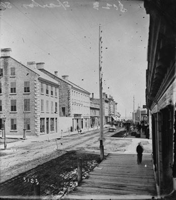 hopping on Sparks Street circa 1865-68, you can see why some people might have been appalled at the choice of Ottawa as Canada's capital. Dirt roads and wooden sidewalks to keep you out of the mud -- and this was after the federal government money started pouring in!
