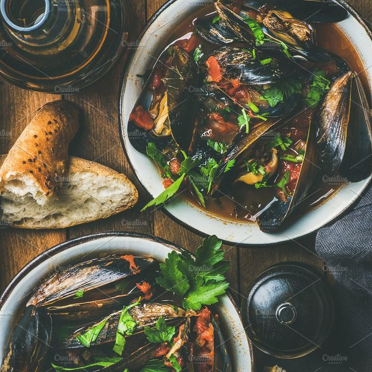 #Belgian boiled mussels in tomato sauce with parsley square crop  Belgian boiled mussels in tomato sauce with fresh parsley in serving metal bowls baguette bread slices and light beer over dark background top view square crop