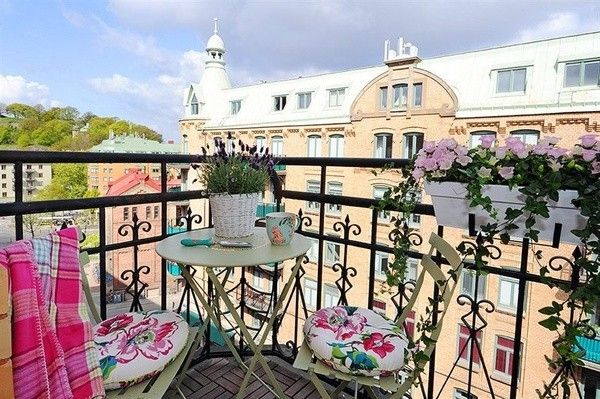 Подвесные горшки с цветами в месте для отдыха на балконе