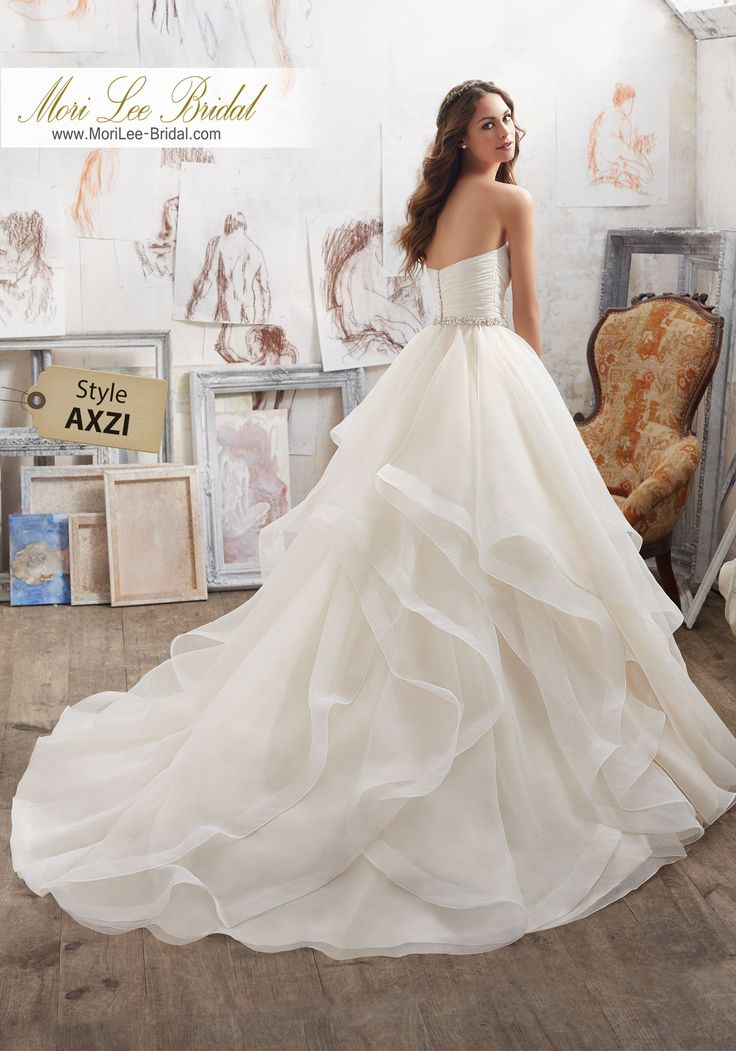 Style AXZI Marissa Wedding Dress  This Dreamy Organza Ballgown Features a Flounced Skirt with Horsehair Trim. Removable Crystal Beaded Satin Belt Included . Available in Three Lengths: 55″, 58″, 61″. Colors Available: White, Ivory, Ivory/Light Gold.