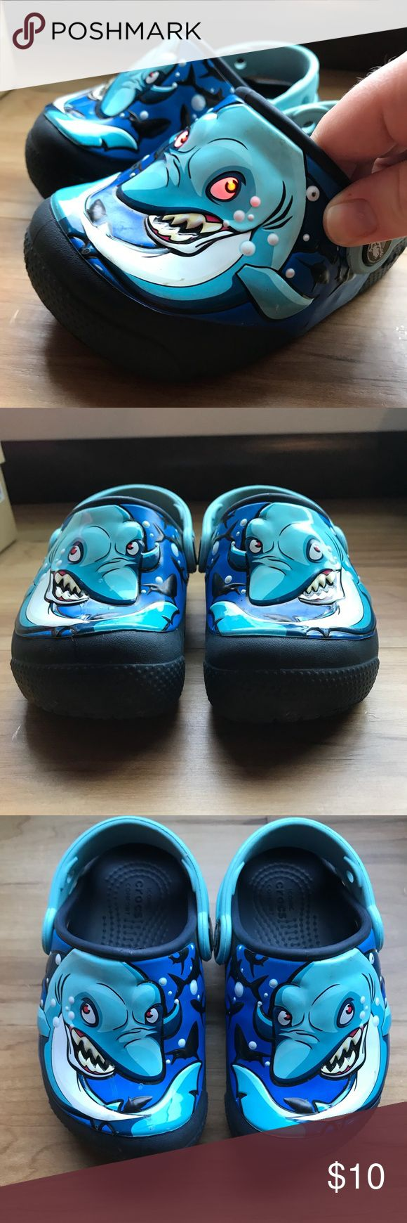 """Crocs """"light up"""" shark eye toddler close toe SZ 7 These were hands down my son's favorite shoes! Blue and vibrantly colored sharks have light up eyes when they step. These are so cute on!   Feel free to bundle these with my other size 7 toddler boys shoes and I will quote a deal! CROCS Shoes"""