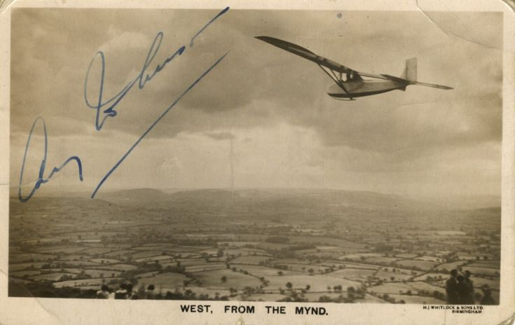 JOHNSON AMY: (1903-1941) English Pioneer Aviatrix. Vintage signed sepia postcard photograph, the image depicting Johnson piloting her glider over the Shropshire countryside and the Long Mynd. Signed ('Amy Johnson') in bold blue fountain pen ink with her name alone across a light area of the image.