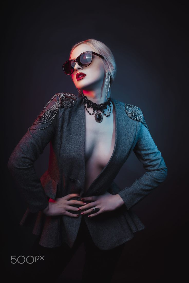 Glamorous blonde woman wearing glasses and dressed in jacket