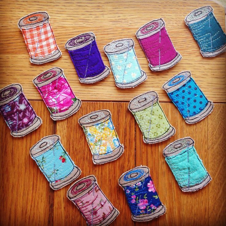 Thread spools with needle brooches. Made with freehand machine embroidery and appliqué