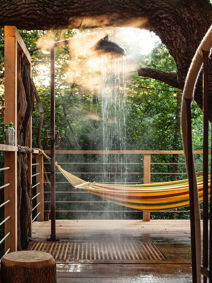 This adult treehouse has an outdoor shower that drains down to the ground below, and a hammock provides a spot to relax on a nice day.