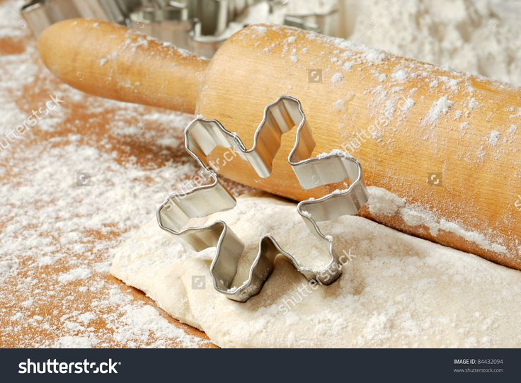 Snowflake cookie cutter with wooden rolling pin and cookie dough dusted with flour.   Macro with shallow dof.