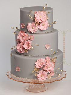 Bellísimo pastel en tono gris con flores rosas y dorado.