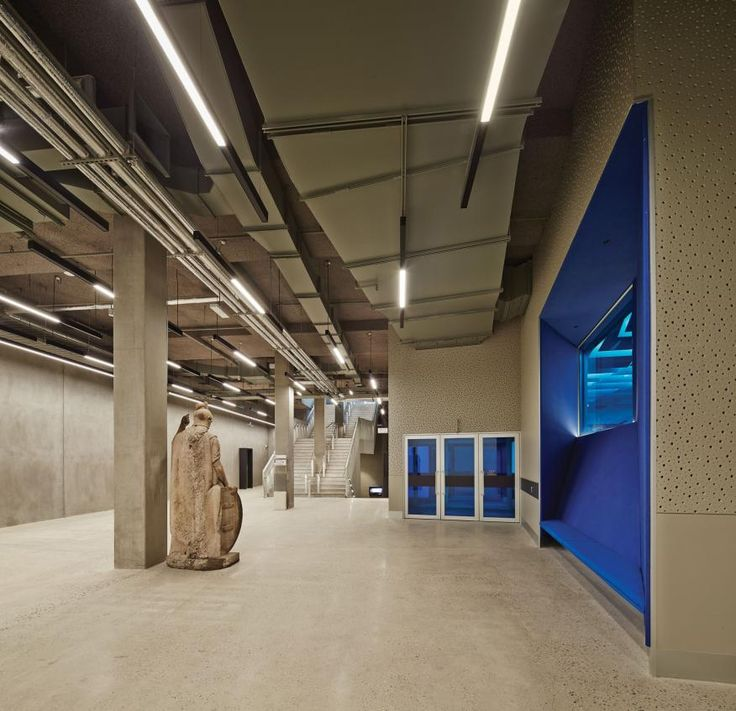 On the basement level, acoustic wallcovering helps control sound in the area outside the main auditorium, seen through the blue glass. Concrete and ductwork are left exposed throughout the structure.