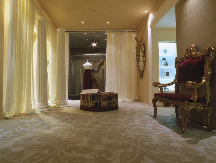 This elegant area reflects the philosophy of the project with  references of literature, theater, architecture, aristocratic and popular traditions, art and craft come together in a big space. The stone flooring is light in color, then softer is the contrast with the white of rampant lions that decorate it. #boutique #fashion #design #viadellaspiga  #contemporary #tradition #aristocratic #interior #design #ideas  #decoration #stone #curtains #mirror #armchair #white #golden  #floor #lions