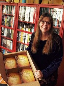 Carol Sill holds the first box of printed books