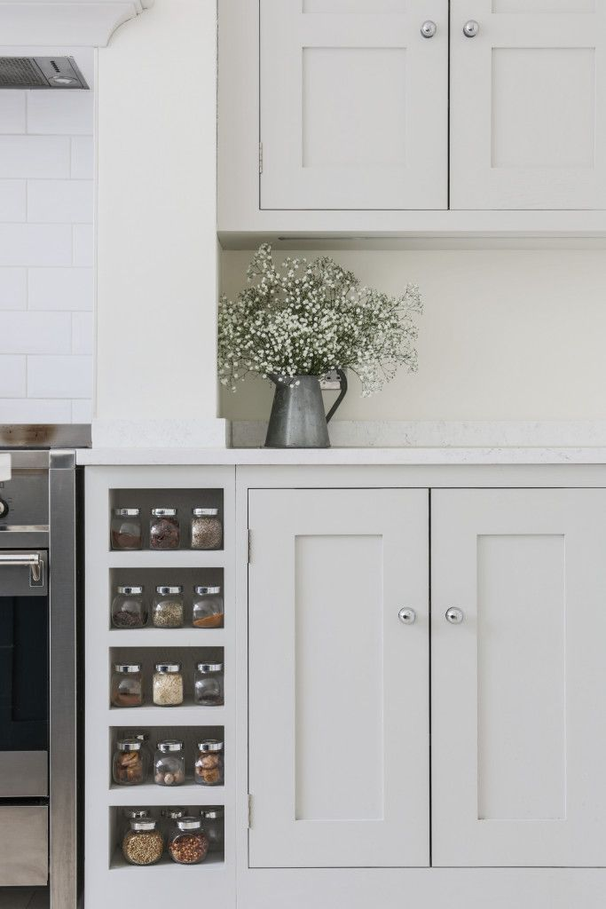 Oak shaker style cabinetry painted in Farrow & Ball Ammonite with built in spice racks on both sides of the Smeg range cooker. The worktop is Bianco Fantasia.