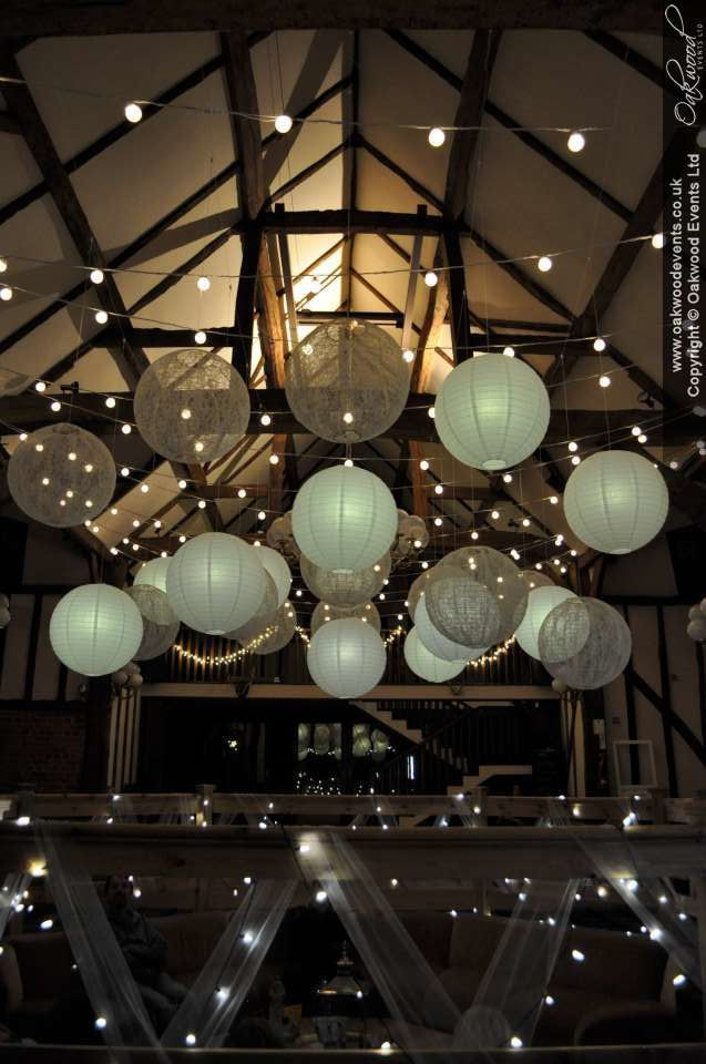 Festoon lights and paper lanterns in the barn at Hillfields Farm. Perfect summer wedding lighting!