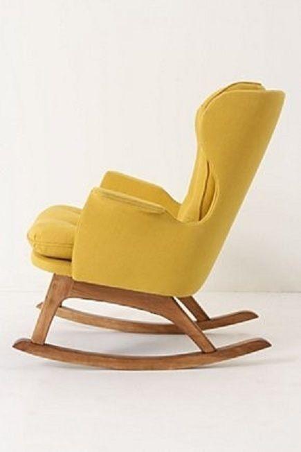 Okerkleurige schommelstoel in oorfauteuilmodel met houten onderstel.