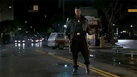 Chris Tucker / Крис Такер, стоя на дороге, в ночном городе танцует и что - то угрожающе кричит, фильм Rush Hour / Час пик